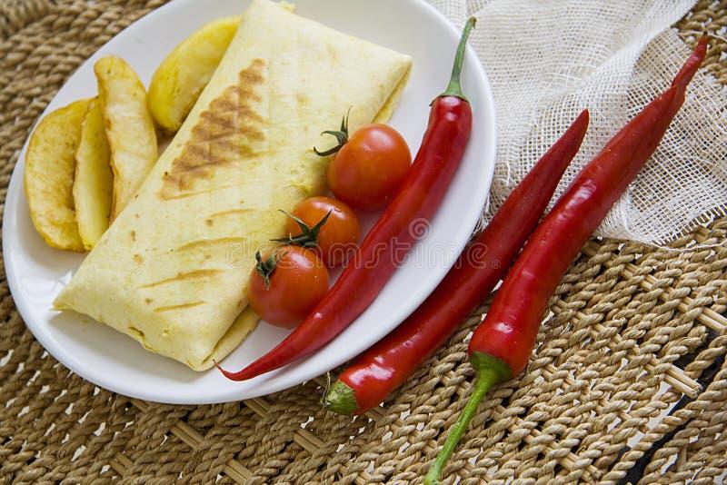 Hete burrito en gebraden die aardappel met tomaat en Spaanse peper wordt gediend royalty-vrije stock afbeeldingen