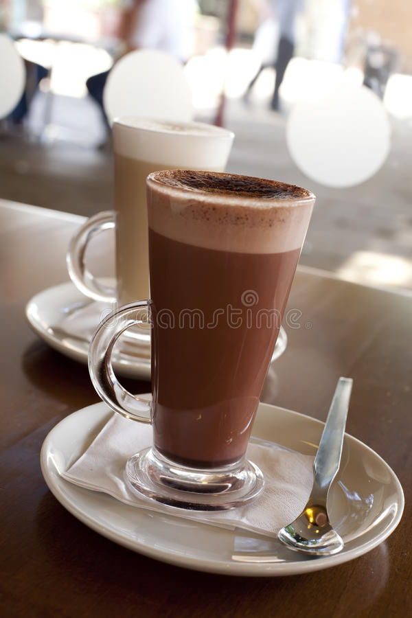 Hete chocolade in een lange klasse met Koffie Latte stock afbeeldingen