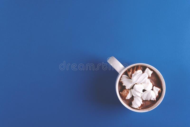 Hete chocolade met heemstsuikergoed op blauwe document achtergrond Hoogste mening De ruimte van het exemplaar royalty-vrije stock fotografie