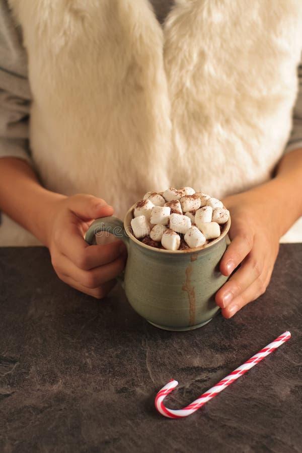 Hete chocolade met mini-marshmallows in kinderhanden stock foto