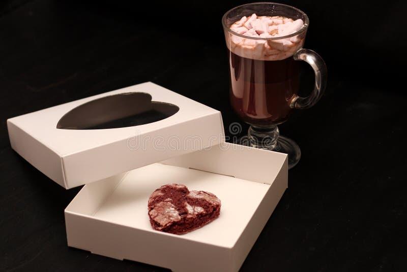 hete drank in een glaskop met roze heemst en witte doos met een transparante dekking in de vorm van hart met koekjes royalty-vrije stock afbeeldingen