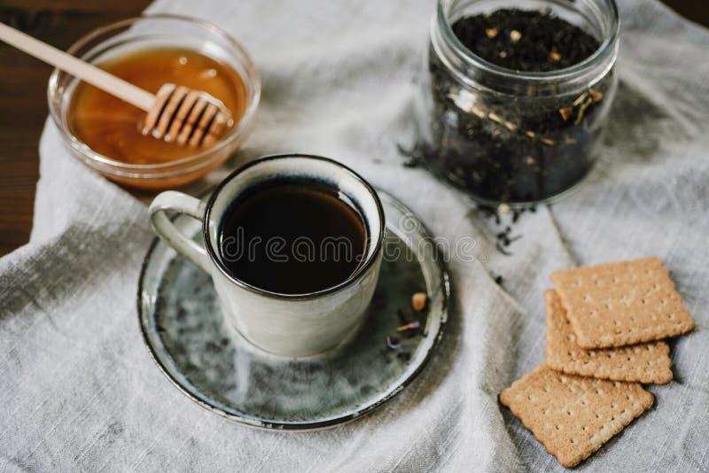 Hete drank en snoepjes Kop, honing, koekjes en theebladen over t royalty-vrije stock foto's