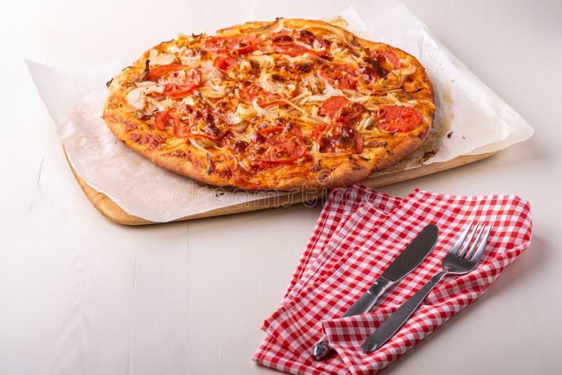 Hete eigengemaakte pizza met kippenvlees, tomaten, uien dichtbij met bestekvork en mes op rood tafelkleed, hoekmening royalty-vrije stock afbeelding