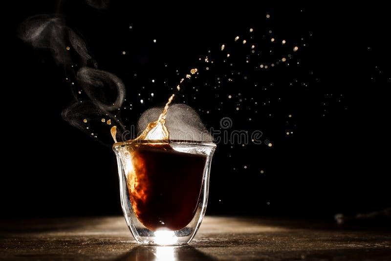 Hete en aromatische koffie die van glaskop morsen stock foto's