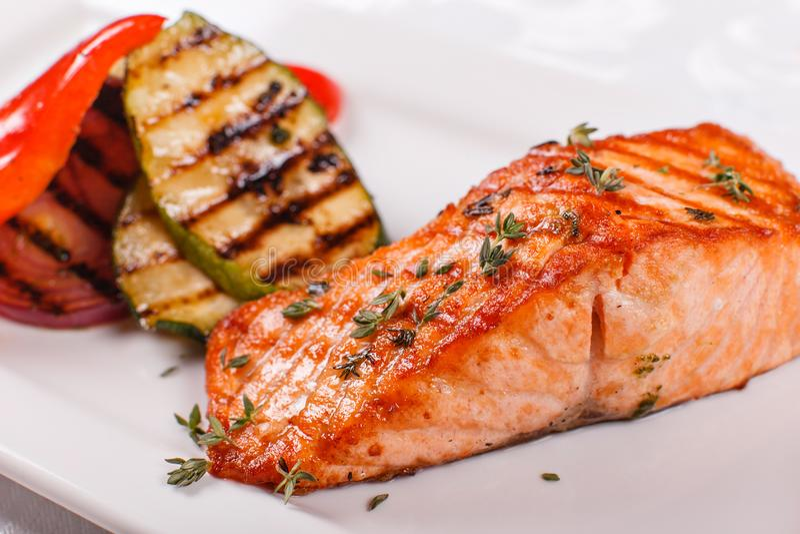 Hete en kruidige filet rode vissen Geroosterde lapje vleeszalm of forel met grillpaprika en courgette Gezond voedsel, zeevruchten royalty-vrije stock foto