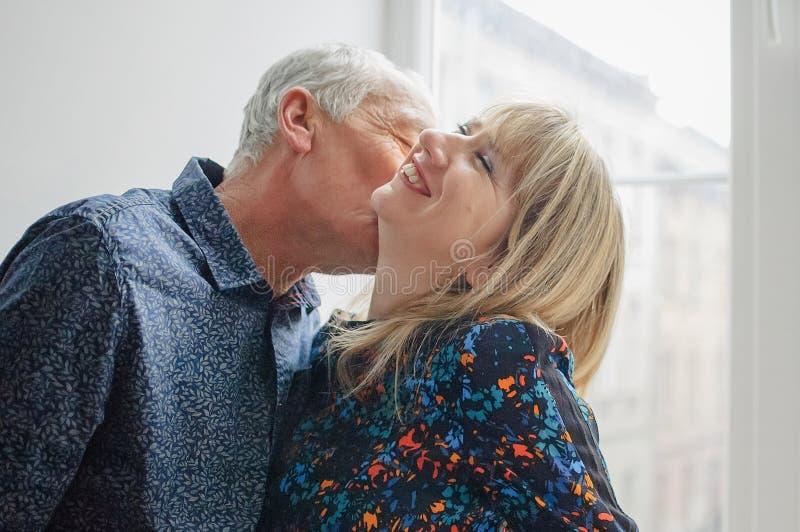 Hete en Sexy Vrouw die Op middelbare leeftijd van het Kussen van Haar Bejaarde Echtgenoot genieten die zich dichtbij Geopend Vens royalty-vrije stock afbeelding