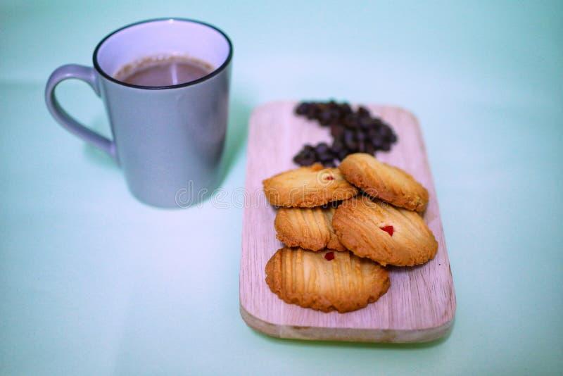 Hete espresso in koppen en boterkoekjes en koffiebonen die op een houten scherpe raads Groene achtergrond worden geplaatst stock fotografie