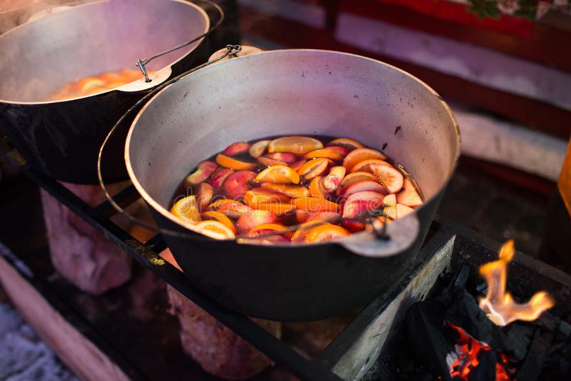 Hete gluhwein of overwogen wijn in een ketel bij eerlijke, lokale traktatie, warm en kruidig Een hete gezonde traditionele citrus stock foto's