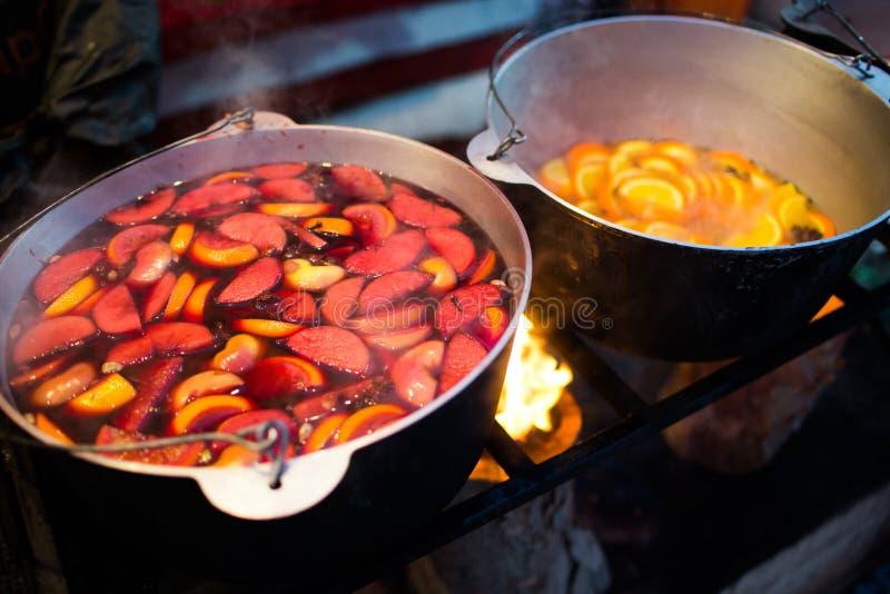 Hete gluhwein of overwogen wijn in een ketel bij eerlijke, lokale traktatie, warm en kruidig Een hete gezonde traditionele citrus stock afbeeldingen