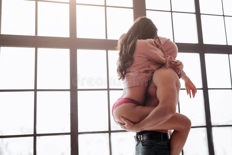 Hete jonge paartribune bij venster en huidenhoofden onder sweater De vrouw zit op kerel en omhelst hem met benen De mens houdt ha royalty-vrije stock foto's
