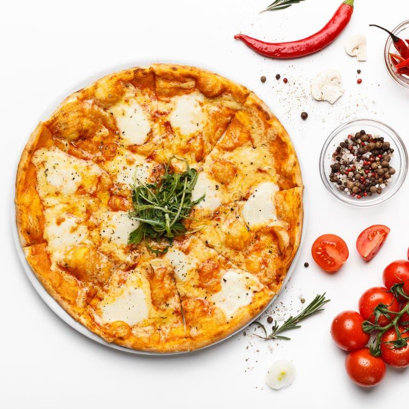 Hete kaasachtige Italiaanse pizza en kruiden op witte lijst royalty-vrije stock foto's
