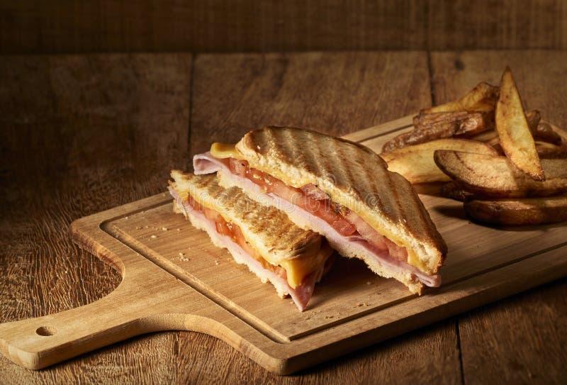 Hete kaassandwich, tomaten en ham met rustieke aardappels stock afbeeldingen