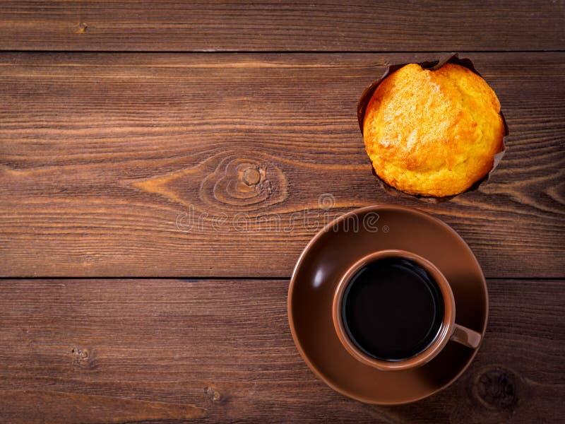 Hete koffie in een Kop op een schotel, zoete smakelijke muffin, op bruine wo royalty-vrije stock afbeeldingen