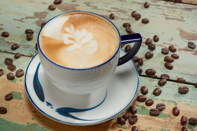 Hete koffie latte kunst in kop op lijst stock foto's