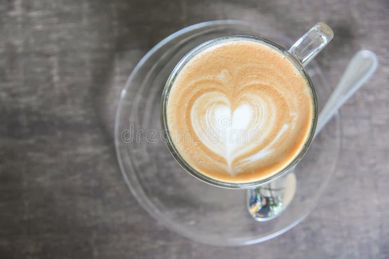 Hete koffie latte met mooie het hartvorm van de schuimkunst op houten lijst bij koffiewinkel royalty-vrije stock fotografie