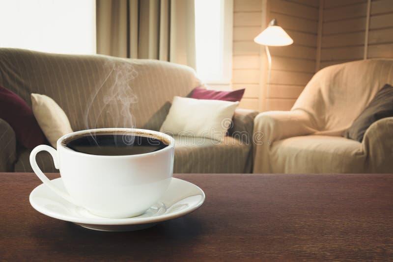 Hete koffie op tafelblad in moderne woonkamer in rustieke stijl met stoel, zachte divan royalty-vrije stock foto's