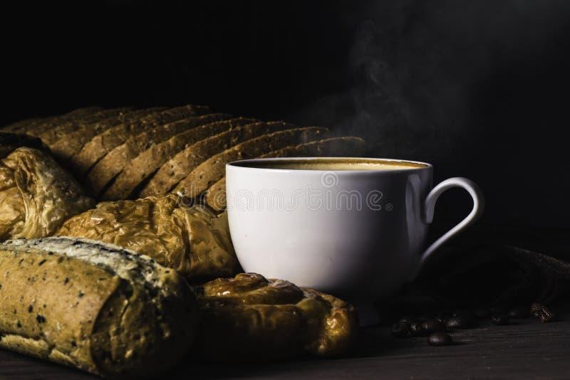 Hete koffie in witte die kop met rook, met bakkerij en koffiebonen in hennepzak op donkere bruine houten lijst, Schoonheidsconcep stock afbeeldingen
