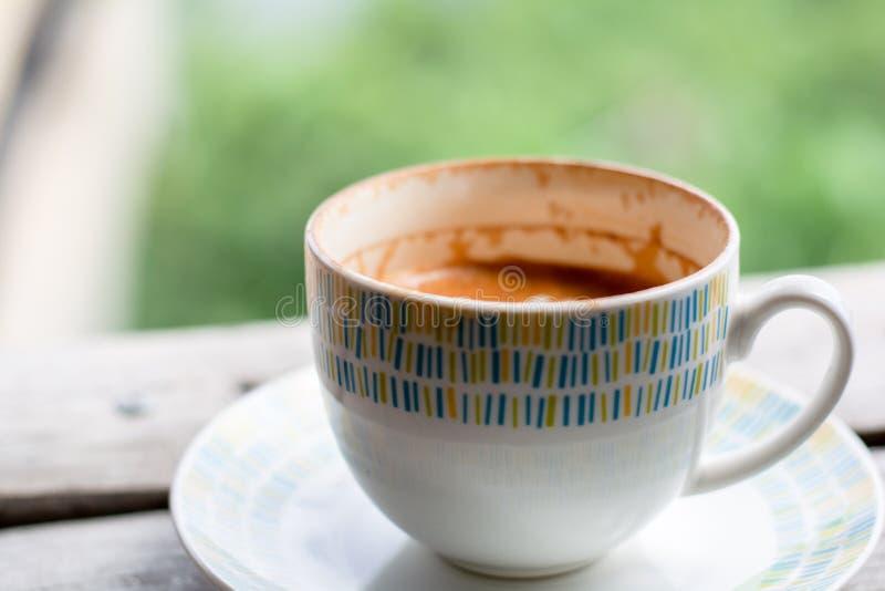 Hete koffieespresso, cappuccino, latte in ceramische witte kop op houten lijst met onscherpe groene aard met exemplaarruimte voor stock foto