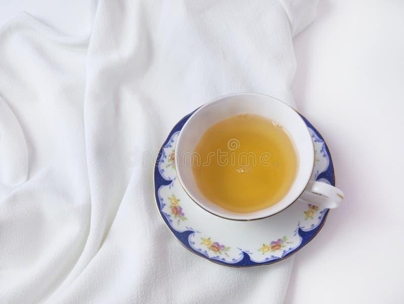 Hete kop van groene thee in de witte decoratieve kop van China op witte achtergrond Vlak leg Hoogste mening stock foto