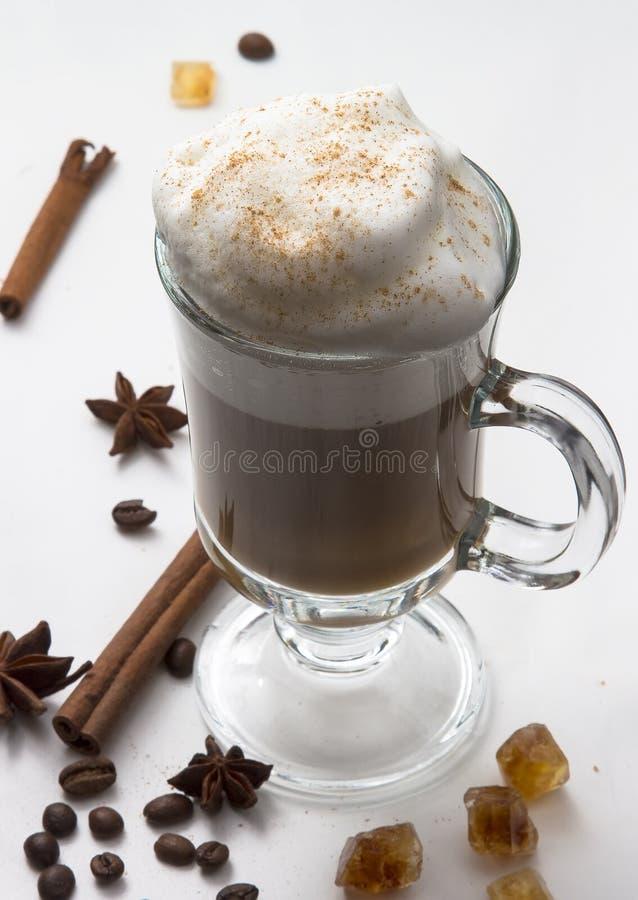 Hete Kop van koffie met geranseld melkschuim op de witte achtergrond met pijpjes kaneel, sterren van anijsplant en royalty-vrije stock foto's