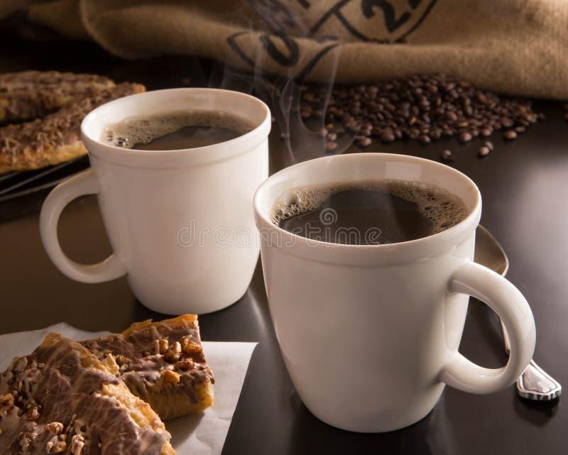 Hete koppen van koffie met bakkerij en koffiebonen door een jutezak stock fotografie