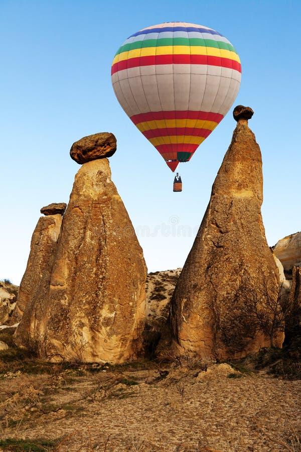 Hete lucht die baloon over spectaculaire steenklippen vliegen in Cappadocia stock fotografie