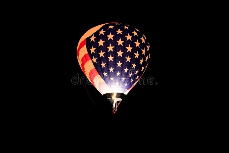 Hete luchtballon in Amerikaanse vlagkleuren en patroon die binnen tegen een zwarte achtergrond van nachthemel gloeien royalty-vrije illustratie