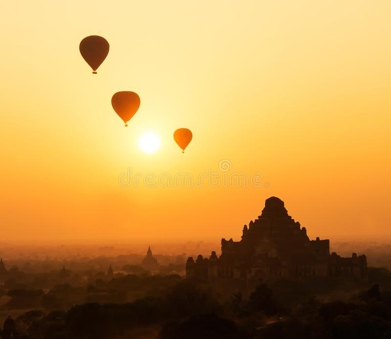 Hete luchtballon in de ochtendhemel op de achtergrond van het overzicht van oude Boeddhistische tempel in Bagan, Myanmar stock afbeeldingen