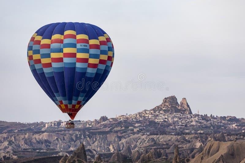 Hete luchtballon die met Uchisar-kasteel op achtergrond vliegen stock foto