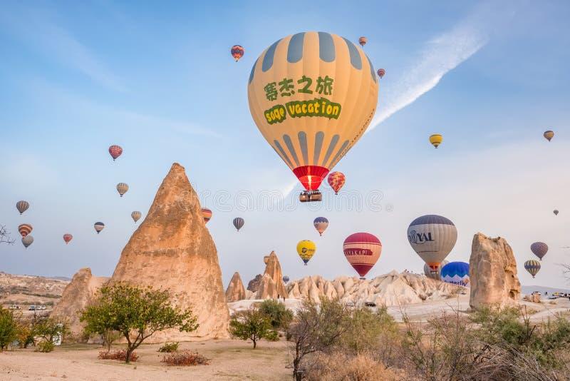 Hete luchtballon die over het beroemde landschap van rotsvormingen in Cappadocia bij zonsopgang vliegen, Turkije royalty-vrije stock fotografie