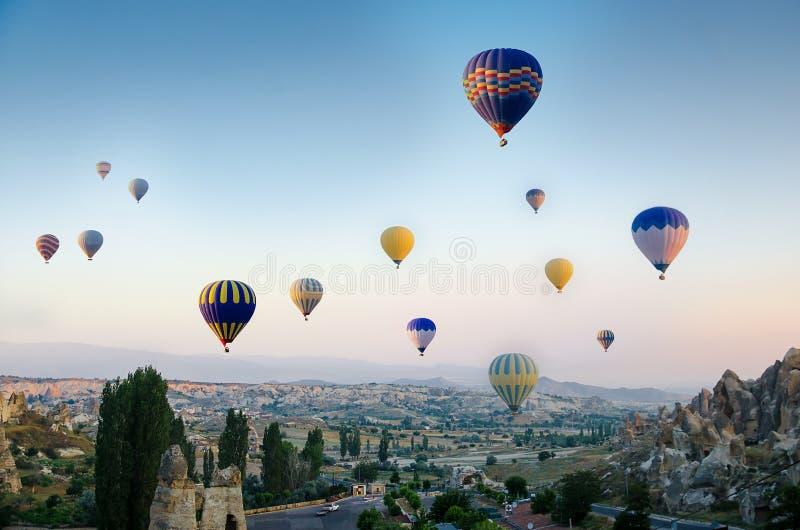 Hete luchtballon die over rotslandschap in Cappadocia Turkije vliegen royalty-vrije stock afbeelding