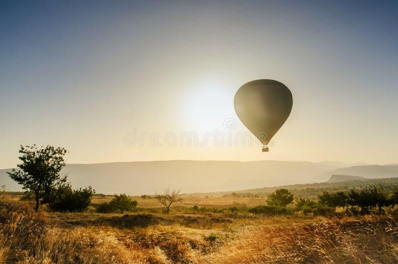 Hete luchtballon die over rotslandschap in Cappadocia Turkije vliegen royalty-vrije stock foto's