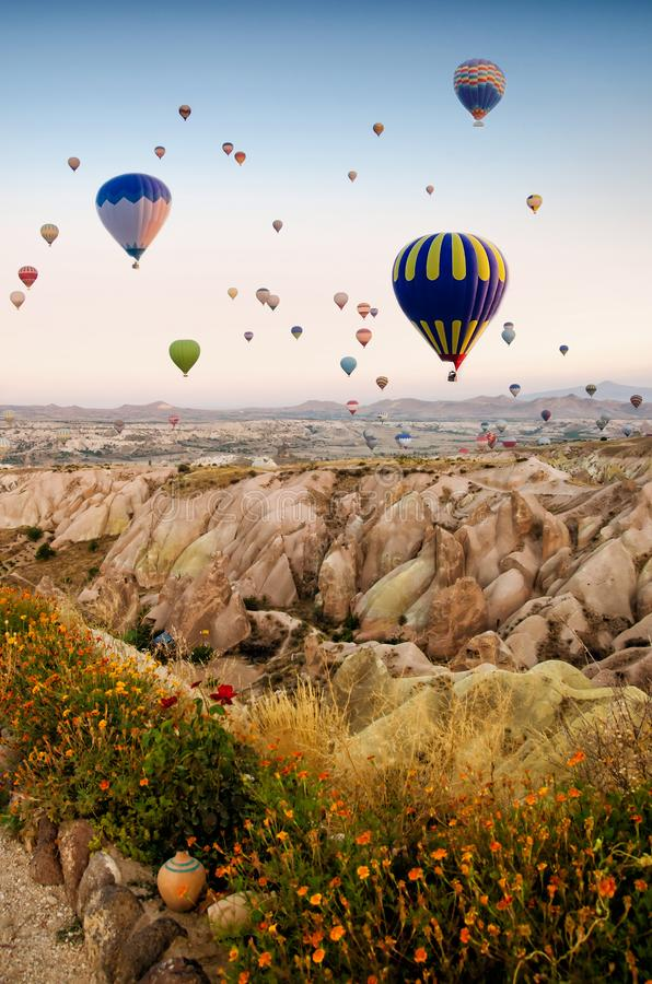 Hete luchtballon die over rotslandschap in Cappadocia Turkije vliegen stock foto