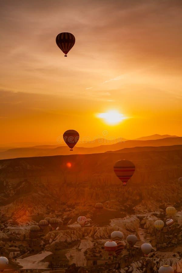 Hete luchtballon die over rotslandschap in Cappadocia Turkije vliegen stock foto's