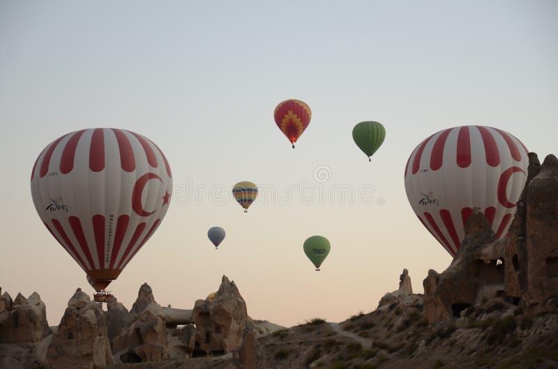 Hete luchtballon die over rotslandschap in Cappadocia Turkije vliegen stock afbeeldingen