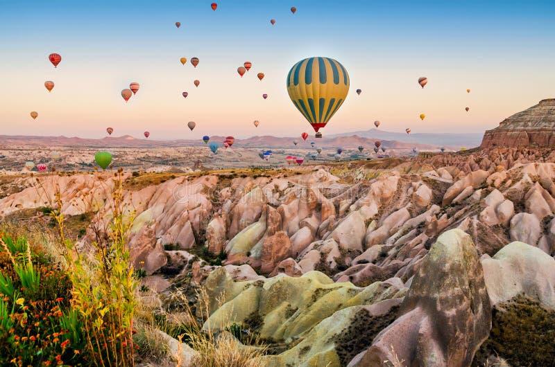 Hete luchtballon die over rotslandschap in Cappadocia Turkije vliegen royalty-vrije stock afbeeldingen