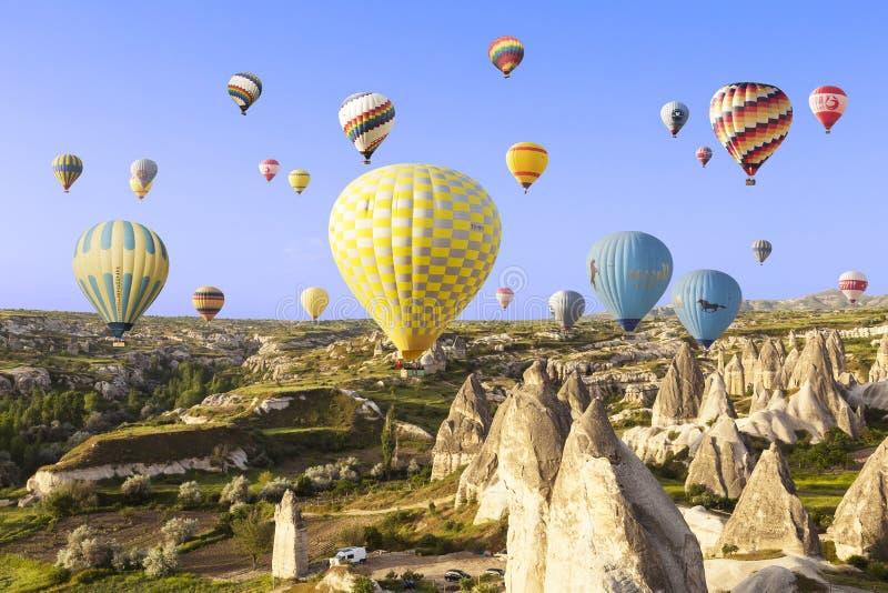 Hete luchtballon die over rotslandschap in Cappadocia vliegen stock afbeeldingen