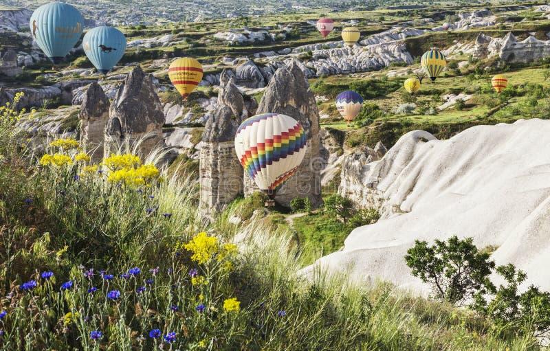 Hete luchtballon die over rotslandschap in Cappadocia vliegen stock fotografie