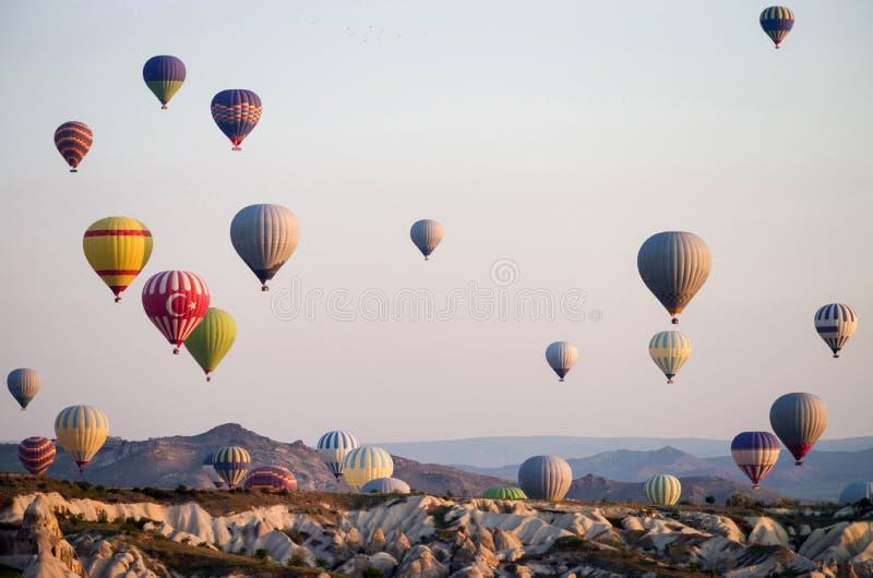 Hete luchtballons die bij zonsopgang over Cappadocia, Turkije vliegen Een ballon met een vlag van Turkije royalty-vrije stock foto's