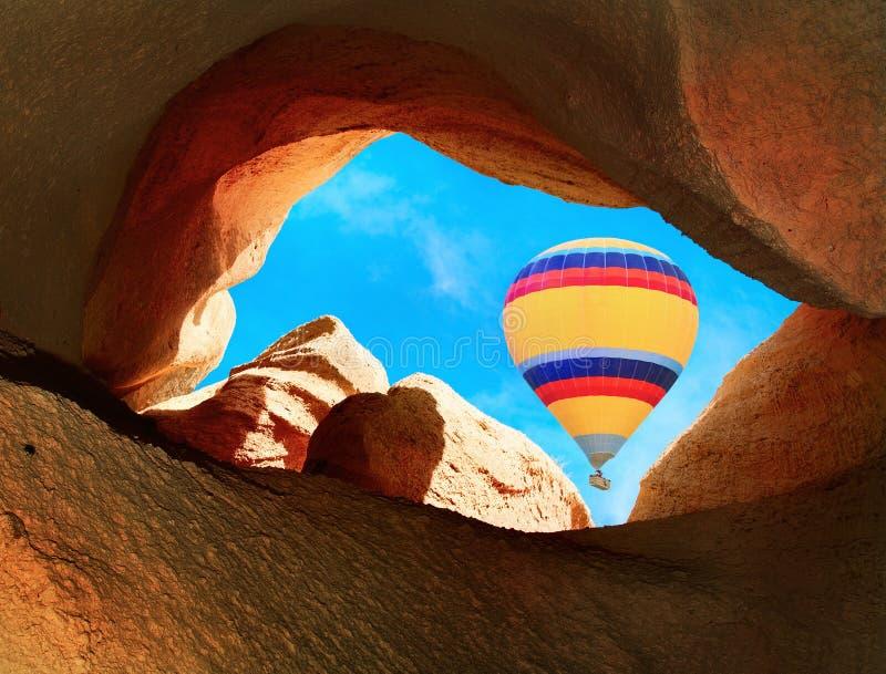 Hete luchtballons die over bergen in Cappadocia vliegen royalty-vrije stock fotografie