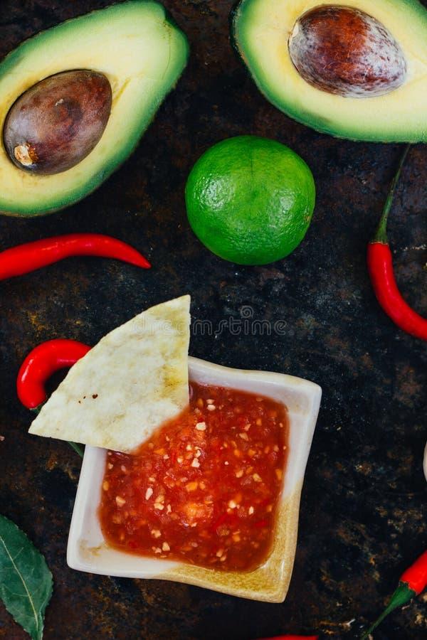 Hete Mexicaanse die salsa whith de nachospaanders door ingrediënten worden omringd - tomaten, Spaanse peperpeper, kalk royalty-vrije stock afbeeldingen