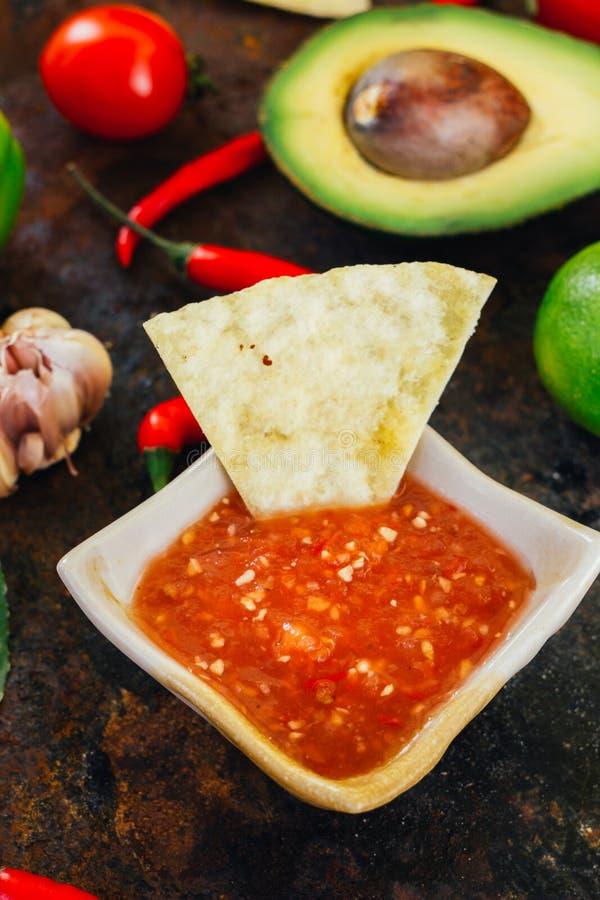 Hete Mexicaanse die salsa whith de nachospaanders door ingrediënten worden omringd - tomaten, Spaanse peperpeper, kalk royalty-vrije stock foto's