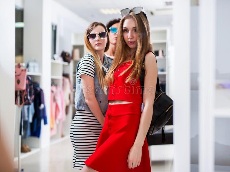 Hete modieuze jonge vrouwen die glazen stellen dragen die in spiegel kijken die zich in womenswear boutique bevinden royalty-vrije stock afbeelding