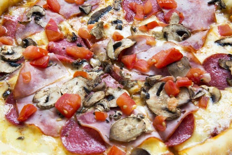 Hete pizza met tomaten, bacon, salami, kaas en paddestoelen, close-up stock foto