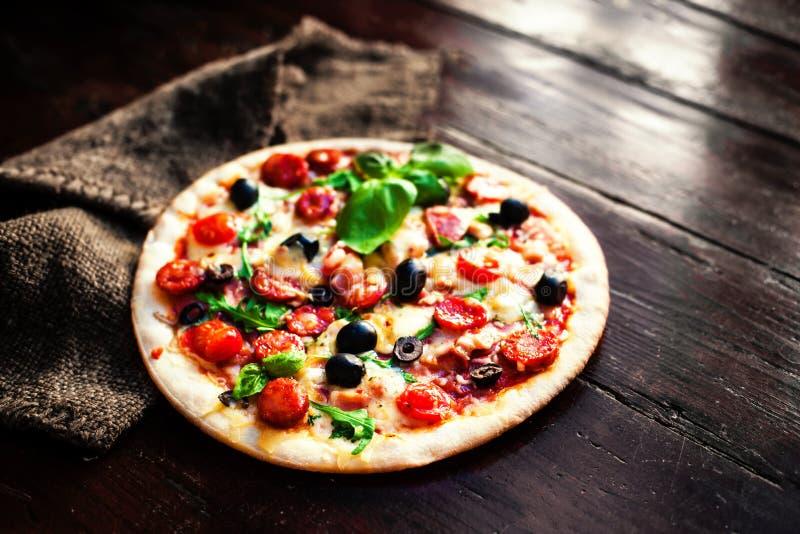 Hete pizza met vlees, basilicum en mozarellakaas op een donkere backgr stock fotografie
