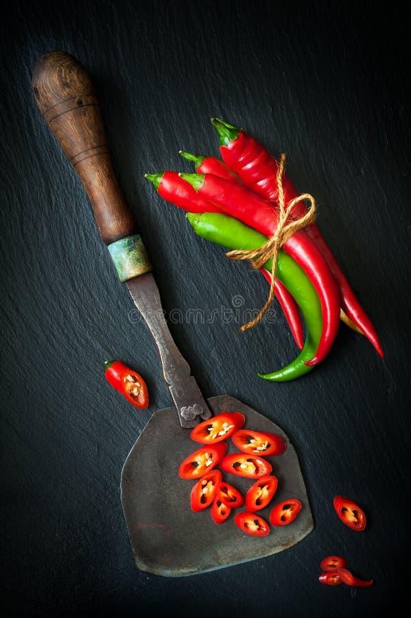 Hete Spaanse peperpeper en uitstekend mes voor het hakken van kruiden op een leibord royalty-vrije stock foto