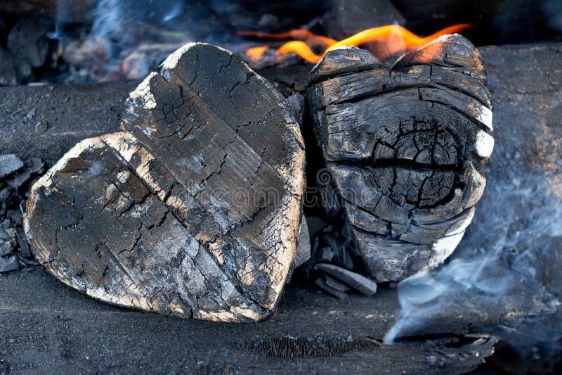 Hete steenkolen en brandhouten in de vorm van menselijk hart Het gloeien en vlammende houtskool, heldere rode brand en as close-u stock fotografie