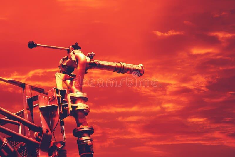 Hete temperatuur, firetruck de hoge druk van de watercanon op dramatische rode hemel stock fotografie