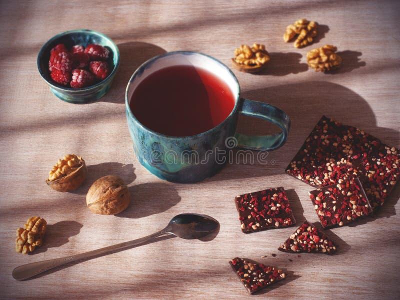 Hete thee en eigengemaakte chocolade met noten en frambozen op houten achtergrond, lichtjes hoogste mening stock foto