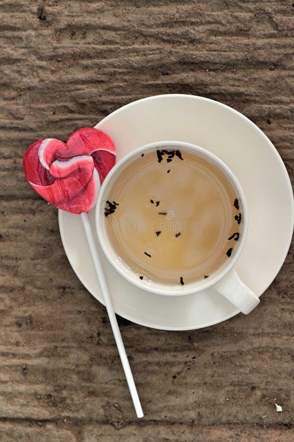 Hete thee in glas en suikergoed zoet valentijnskaartenhart stock foto's